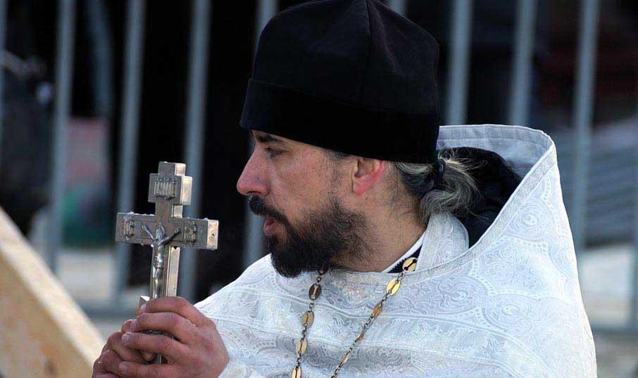 Священник читает молитву - фото darunok.ua